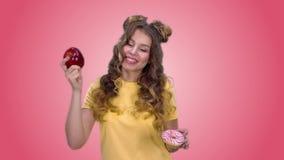 Το όμορφο νέο κορίτσι σε μια κίτρινη μπλούζα κάνει μια επιλογή υπέρ των υγιών προϊόντων και του χαμόγελου απόθεμα βίντεο
