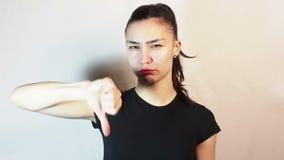 Το όμορφο νέο κορίτσι σε μια μαύρη μπλούζα παρουσιάζει αντίχειρα κάτω και τινάζει το κεφάλι της στην αποστροφή απόθεμα βίντεο