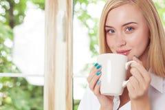 Το όμορφο νέο κορίτσι στηρίζεται στο windowsill Στοκ Εικόνες