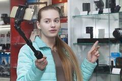 Το όμορφο νέο κορίτσι στο επαγγελματικό κατάστημα εξοπλισμού φωτογραφιών καταγράφει το βίντεο στο τηλέφωνο χρησιμοποιώντας selfie στοκ φωτογραφία με δικαίωμα ελεύθερης χρήσης