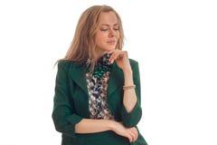 Το όμορφο νέο κορίτσι στο σακάκι κρατά το χέρι σας κοντά στο πηγούνι σας και κοιτάζει επίμονα κάτω Στοκ φωτογραφία με δικαίωμα ελεύθερης χρήσης
