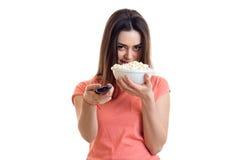 Το όμορφο νέο κορίτσι τρώει pop-corn και τη TV προσοχής Στοκ φωτογραφία με δικαίωμα ελεύθερης χρήσης