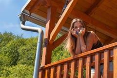 Το όμορφο νέο κορίτσι χρωματίζει ένα ξύλινο gazebo Θερινή εργασία στον κήπο Το όμορφο brunette ντύνει τις ξύλινες ακτίνες Στοκ Φωτογραφίες