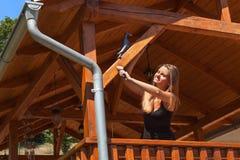 Το όμορφο νέο κορίτσι χρωματίζει ένα ξύλινο gazebo Θερινή εργασία στον κήπο Το όμορφο brunette ντύνει τις ξύλινες ακτίνες Στοκ Φωτογραφία