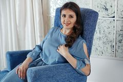 Το όμορφο νέο κορίτσι brunette σε ένα μπλε φόρεμα κάθεται σε ένα BL Στοκ εικόνα με δικαίωμα ελεύθερης χρήσης