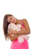 Το όμορφο νέο κράτημα γυναικών teddy αντέχουν και το αγκάλιασμα τον που χαμογελά Στοκ Εικόνα