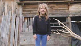 Το όμορφο νέο ξανθομάλλες μικρό κορίτσι θέτει σε ένα ξύλινο τοπίο αγροτών απόθεμα βίντεο
