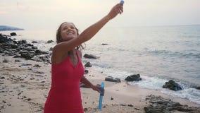 Το όμορφο νέο παιχνίδι γυναικών brunette με το σαπούνι βράζει στην τροπική παραλία στο χρόνο ηλιοβασιλέματος κίνηση αργή 1920x108 απόθεμα βίντεο