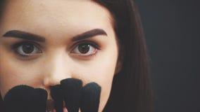 Το όμορφο νέο όμορφο πορτρέτο κοριτσιών είναι χαρούμενο όμορφο Μια γυμνή γυναίκα θέτει με μια βούρτσα makeup και εξετάζει απόθεμα βίντεο