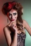 Το όμορφο νέο προκλητικό κορίτσι με την πολύβλαστη τρίχα θεατρικό σε αναδρομικό κοιτάζει με το κόκκινο καπέλο στο φωτεινό makeup  Στοκ Εικόνες