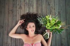 Το όμορφο νέο υγιές κορίτσι με μια ανθοδέσμη βρίσκεται στην πράσινη σειρά Στοκ φωτογραφία με δικαίωμα ελεύθερης χρήσης