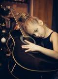Το όμορφο νέο λυπημένο κορίτσι αγκαλιάζει μια κιθάρα Στοκ Φωτογραφίες