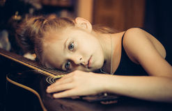 Το όμορφο νέο λυπημένο κορίτσι αγκαλιάζει μια κιθάρα Στοκ Εικόνες