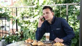 Το όμορφο νέο χαμογελώντας άτομο κάθεται σε έναν καφέ που μιλά στο cappuccino τηλεφωνικής κατανάλωσης φιλμ μικρού μήκους