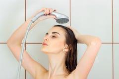 Το όμορφο νέο brunette πλένει την τρίχα της στο ντους Στοκ φωτογραφία με δικαίωμα ελεύθερης χρήσης