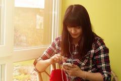 Το όμορφο νέο brunette σε ένα πουκάμισο καρό χρησιμοποιεί ένα smartphone Στοκ εικόνες με δικαίωμα ελεύθερης χρήσης