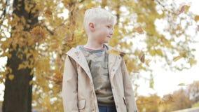 Το όμορφο ξανθό αγόρι στέκεται στο πάρκο φθινοπώρου απόθεμα βίντεο