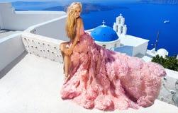 Το όμορφο ξανθό θηλυκό πρότυπο νυφών στο καταπληκτικό γαμήλιο φόρεμα θέτει στο νησί Santorini στην Ελλάδα Στοκ Φωτογραφία