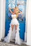 Το όμορφο ξανθό θηλυκό πρότυπο νυφών στο καταπληκτικό γαμήλιο φόρεμα θέτει στο νησί Santorini στην Ελλάδα Στοκ φωτογραφίες με δικαίωμα ελεύθερης χρήσης