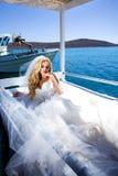 Το όμορφο ξανθό θηλυκό πρότυπο νυφών στο καταπληκτικό γαμήλιο φόρεμα θέτει στο νησί Santorini στην Ελλάδα και πέρα Στοκ Εικόνες