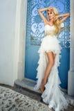 Το όμορφο ξανθό θηλυκό πρότυπο νυφών στο καταπληκτικό γαμήλιο φόρεμα θέτει στο νησί Santorini στην Ελλάδα Στοκ Εικόνες