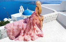 Το όμορφο ξανθό θηλυκό πρότυπο νυφών στο καταπληκτικό γαμήλιο φόρεμα θέτει στο νησί Santorini στην Ελλάδα Στοκ εικόνα με δικαίωμα ελεύθερης χρήσης