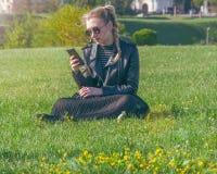 Το όμορφο ξανθό κορίτσι κάθεται σε έναν πράσινο χορτοτάπητα και κοιτάζει σε ένα smartphone Στοκ εικόνα με δικαίωμα ελεύθερης χρήσης