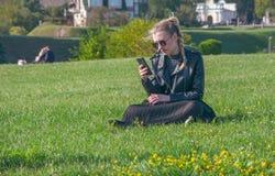 Το όμορφο ξανθό κορίτσι κάθεται σε έναν πράσινο χορτοτάπητα και κοιτάζει σε ένα smartphone Στοκ φωτογραφία με δικαίωμα ελεύθερης χρήσης