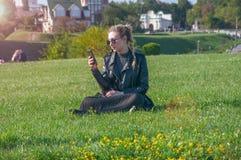 Το όμορφο ξανθό κορίτσι κάθεται σε έναν πράσινο χορτοτάπητα και κοιτάζει σε ένα smartphone Στοκ Φωτογραφία
