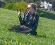 Το όμορφο ξανθό κορίτσι κάθεται σε έναν πράσινο χορτοτάπητα και κοιτάζει σε ένα smartphone Στοκ Εικόνες