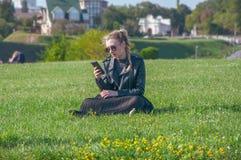Το όμορφο ξανθό κορίτσι κάθεται σε έναν πράσινο χορτοτάπητα και κοιτάζει σε ένα smartphone Στοκ εικόνες με δικαίωμα ελεύθερης χρήσης