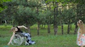 Το όμορφο ξανθό κορίτσι κάθεται στην αναπηρική καρέκλα και έχει τη διασκέδαση με το παιχνίδι και τη ρίψη του frisbee φιλμ μικρού μήκους