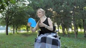 Το όμορφο ξανθό κορίτσι κάθεται στην αναπηρική καρέκλα και έχει τη διασκέδαση με το παιχνίδι και τη ρίψη του frisbee απόθεμα βίντεο