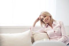 Το όμορφο ξανθό κορίτσι κάθεται στον καναπέ Στοκ Φωτογραφία