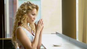 Το όμορφο ξανθό κορίτσι πίνει ένα φλυτζάνι του καυτού καφέ ή του τσαγιού στον καφέ απόθεμα βίντεο