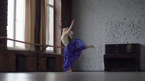 Το όμορφο ξανθό κορίτσι πηδά και κάνει την εκτροπή σε σε αργή κίνηση φιλμ μικρού μήκους