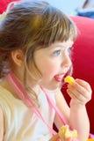 Το όμορφο ξανθό κορίτσι πρόκειται να απολαύσει μια τηγανισμένη πατάτα, καθμένος σε έναν κόκκινο καναπέ με μια γιορτή γενεθλίων στοκ εικόνες