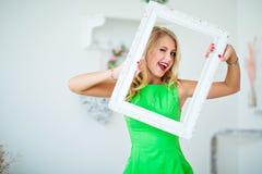 Το όμορφο ξανθό κορίτσι σε ένα πράσινο πλαίσιο εκμετάλλευσης φορεμάτων και κλείνει το μάτι Στοκ εικόνες με δικαίωμα ελεύθερης χρήσης