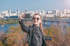 Το όμορφο ξανθό κορίτσι στέκεται στο υπόβαθρο της πόλης και κάνει selfie Στοκ φωτογραφία με δικαίωμα ελεύθερης χρήσης