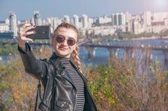 Το όμορφο ξανθό κορίτσι στέκεται στο υπόβαθρο της πόλης και κάνει selfie Στοκ Φωτογραφίες
