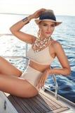 Το όμορφο ξανθό κορίτσι στη καλή φόρμα με τα μακριά σκοτεινά κόκκινα χείλια δερμάτων τρίχας και μαυρίσματος στο κολυμπώντας καπέλ Στοκ εικόνα με δικαίωμα ελεύθερης χρήσης