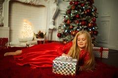 Το όμορφο ξανθό κορίτσι φορά διακοσμημένη φορεμάτων μόδας το κόκκινο πλησίον χριστουγεννιάτικο δέντρο Στοκ Εικόνα