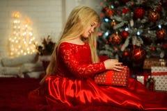 Το όμορφο ξανθό κορίτσι φορά διακοσμημένη φορεμάτων μόδας το κόκκινο πλησίον χριστουγεννιάτικο δέντρο Στοκ Φωτογραφία