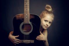 Το όμορφο ξανθό νέο κορίτσι αγκαλιάζει μια κιθάρα Στοκ εικόνες με δικαίωμα ελεύθερης χρήσης