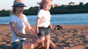 Το όμορφο ξανθό mom κτενίζει την κόρη της στη συνεδρίαση riverbank στην παραλία φιλμ μικρού μήκους