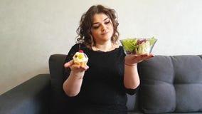 Το όμορφο ολόκληρο κορίτσι κάθεται στον καναπέ ένα κέικ σαλάτας, επιδόρπιο, γλυκό, επιλογή απόθεμα βίντεο