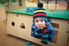 Το όμορφο παιδί κάθεται στο μικρό σπίτι στην περιοχή παιδικών χαρών στοκ φωτογραφίες