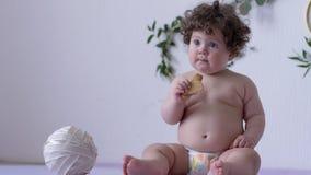 Το όμορφο παχουλό μικρό παιδί με τη σγουρή τρίχα τρώει το μπισκότο στο εσωτερικό στο υπόβαθρο του τοίχου με το ντεκόρ φιλμ μικρού μήκους