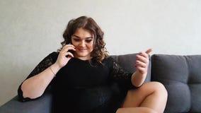 Το όμορφο πλήρες κορίτσι μιλά στο τηλέφωνο στον καναπέ απόθεμα βίντεο
