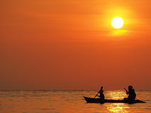 Το όμορφο πορτοκαλί ηλιοβασίλεμα ουρανού defocus θαμπάδων επάνω από τη θάλασσα με τη σκιαγραφία του ατόμου και το αγόρι κωπηλατού Στοκ εικόνες με δικαίωμα ελεύθερης χρήσης